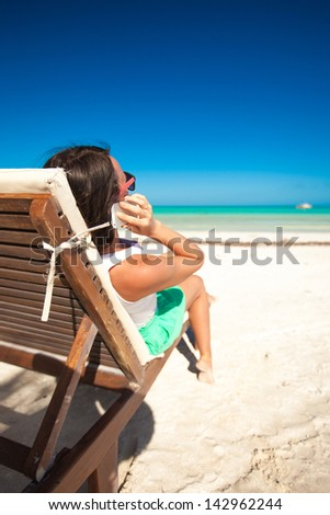 Young woman talking on the phone while sitting on a beach lounger - stock photo