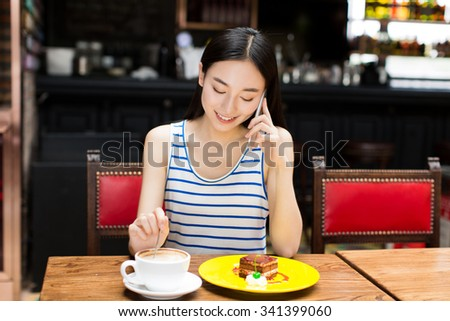young woman talking on the phone with a cake at a coffee shop. - stock photo