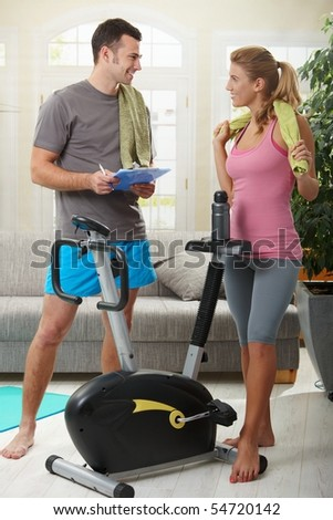 Young woman talking with her personal trainer standing beside exercise bike at home. - stock photo