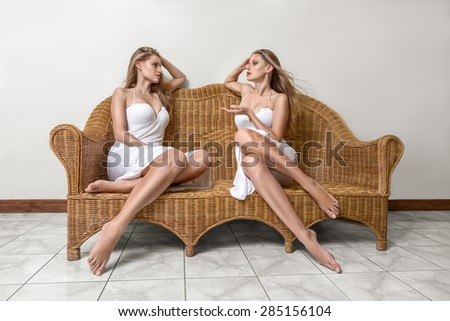 Young woman talking with yourself alter ego sitting on sofa - stock photo