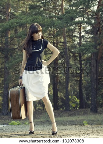 Young woman tand on a trainstation with suitcase in her hand