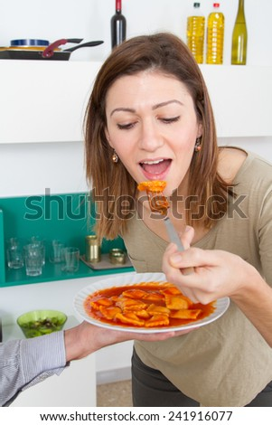 Young woman tasting pasta with tomato sauce