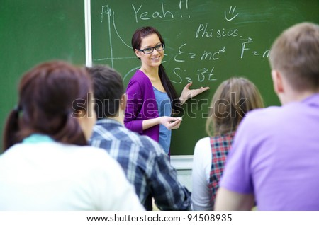 young woman-teacher conducts lessons with a group of students