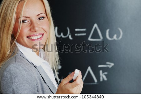 young woman teacher in front of a blackboard - stock photo