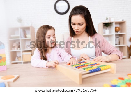 Young woman teaches a little girl math on wooden abacus. The girl is learning to count. Mom helps her.