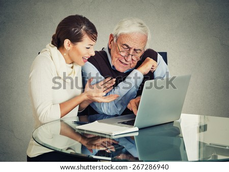 Young woman teaching confused, senior, older, elderly man with eyeglasses how to use laptop. Generation gap differences concept - stock photo