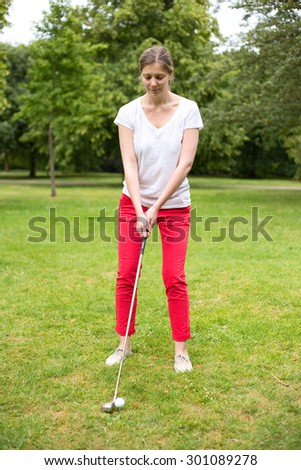 young woman teeing off on the golf course - stock photo