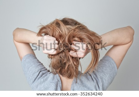 Young woman teen girl pulling her long light hair on white background - stock photo