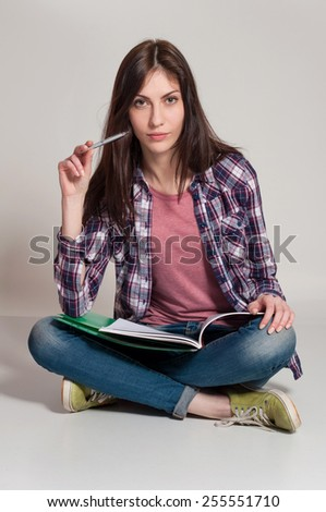 Young woman (teen girl) reading book. Grey background - stock photo
