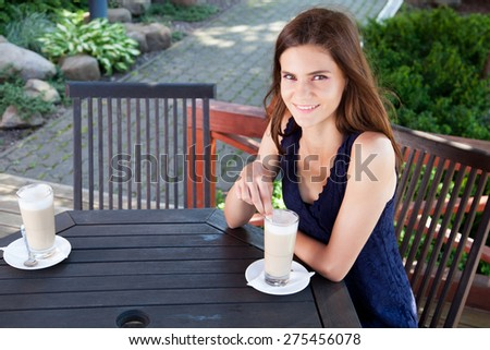 Young woman - teenage girl outdoors sitting at the cafe table with a cup of latte, waiting for someone and smiling.  - stock photo