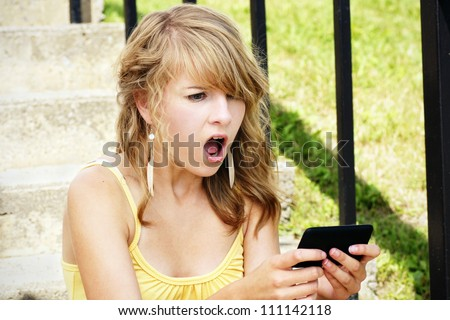 Young woman, teenager girl or student shocked at what she is reading on her cell phone, perfect for online intimidation or bullying at school. - stock photo