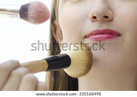 Young woman teenager having make up on her face by other's hands on white background
