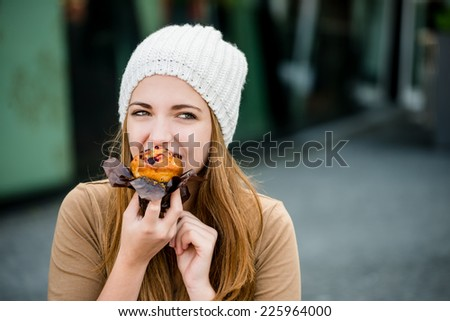 Young woman - teenager in cap eating muffin outdoor in street - stock photo