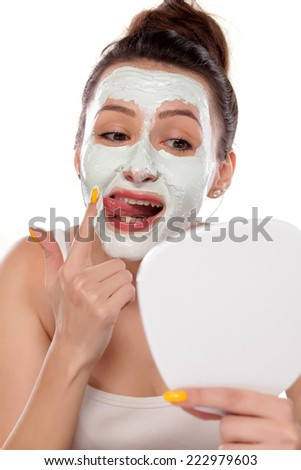 young woman testing a face mask with her tongue