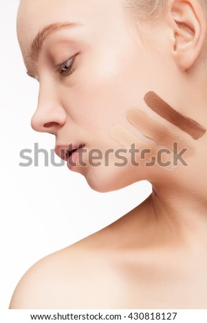 Young woman testing cosmetic products on her skin on white background in studio