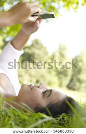 Young Woman Texting Lying In Summer Park