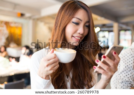 Young woman texting or using smartphone and drinking coffee in the cafe, City lifestyle, cafe lifestyle, Modern life. - stock photo