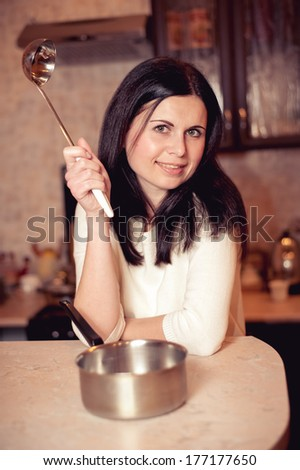 Young woman thinking about a recipe on kitchen - stock photo