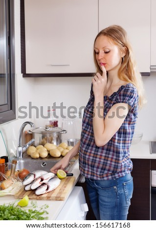 Young woman thinking how to cook fish at kitchen - stock photo