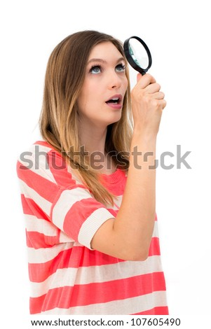 young woman through a magnifying glass with a surprised expression - stock photo