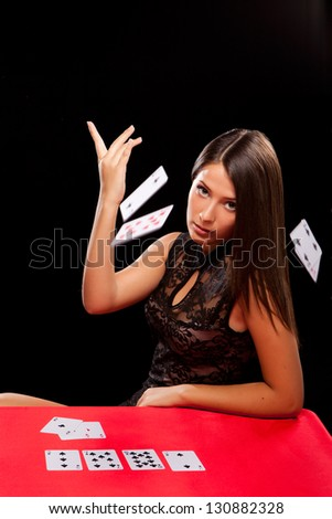 young woman throw playing cards in casino - stock photo