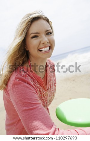 Young woman throwing flying disc on beach - stock photo