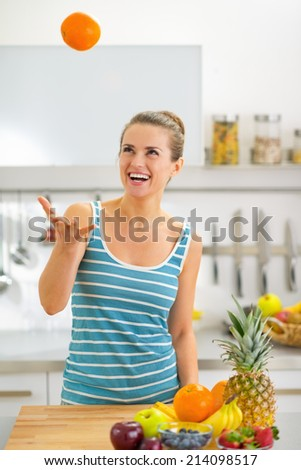 Young woman throwing orange up in kitchen