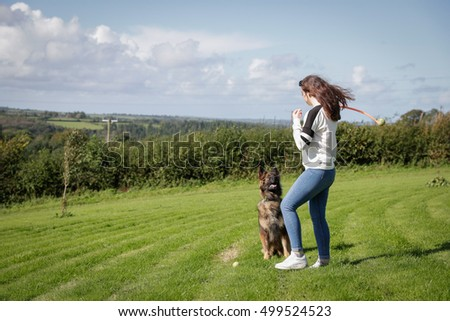 Young woman throws a ball for her pet dog a German Shepherd.
