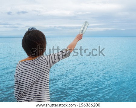Young woman throws a bottle with a wish at sea - stock photo