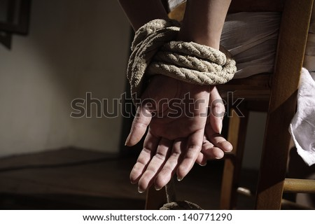 Young woman tied to a chair in a empty room, hands close up - stock photo