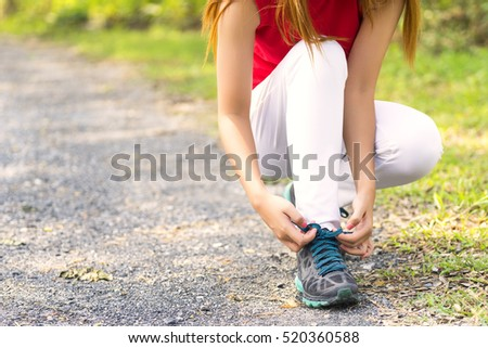 Young woman ties her green shoelaces on concrete in the park