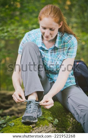 Young woman ties her walking shoe as she sits on a tree log in a remote forest.