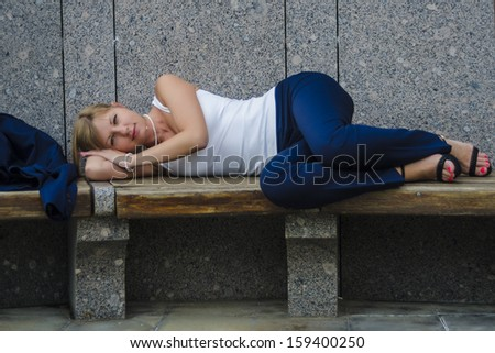 Young woman tired businessman lying on a bench a hard day on the background of a modern business center
