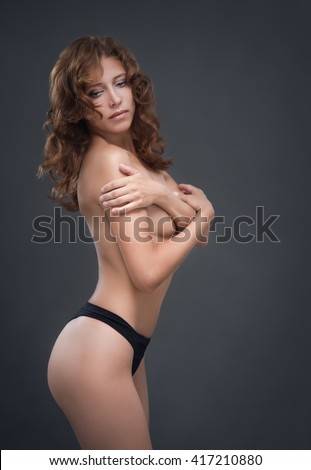 Young woman topless on black background - stock photo