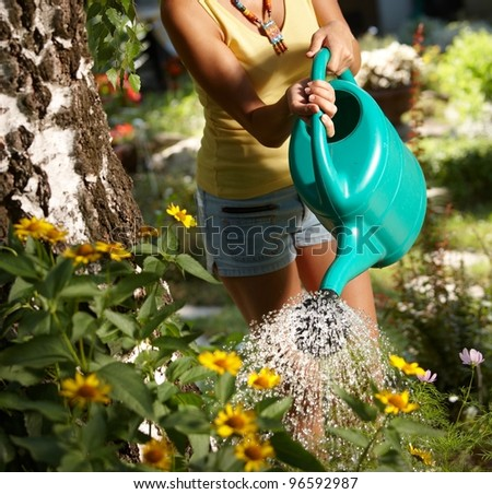 Young woman torso watering plants in the garden at summertime.?