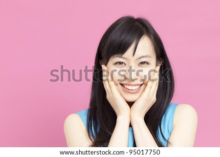 young woman touching her face - stock photo