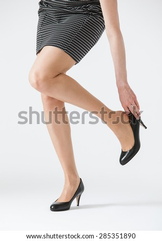Young woman touching her shoe, white background - stock photo