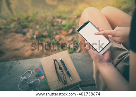 Young woman touching on smartphone blank screen while sitting on wood bench in park in morning time on weekend with vintage filter effect - stock photo