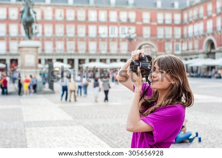 Young woman tourist holding a photo camera and taking picture in Plaza Mayor square, Madrid, Spain. Tourist attraction, statue of Felipe III in the background. - stock photo