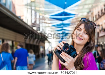 Young woman tourist holding a photo camera, smiling and looking at camera happy in Plaza del Sol square, Madrid, Spain. - stock photo