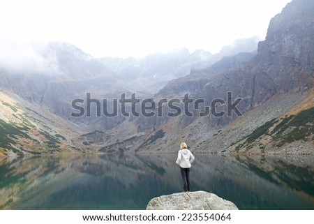 Young woman tourist looking at mountain lake, High Tatra Mountains, Poland, Slovakia