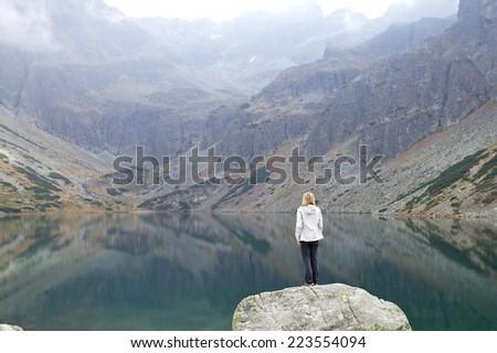 Young woman tourist looking at mountain lake, High Tatra Mountains, Poland, Slovakia - stock photo