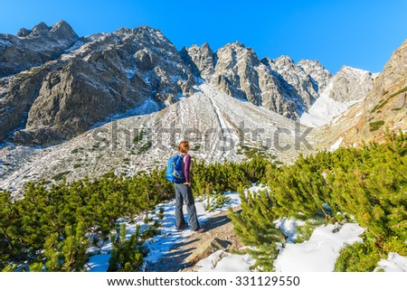 Young woman tourist looking at mountains covered with snow in autumn landscape of Hincova valley, Tatra Mountains, Slovakia
