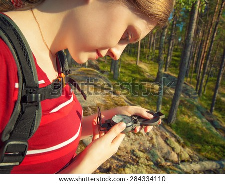 Young woman tourist looking on compass. - stock photo