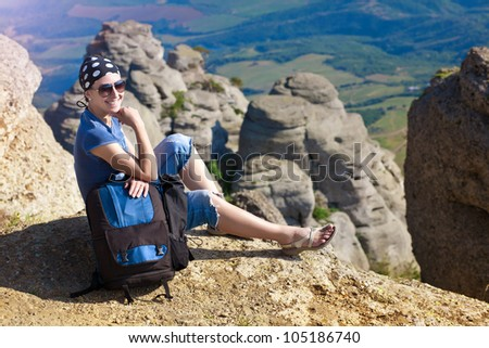 young woman tourist looks for way from the top of the mountain