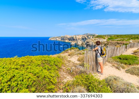 Young woman tourist on coastal path to Bonifacio old town built on high cliff above the sea, Corsica island, France