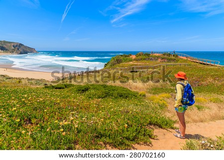 Young woman tourist on walking path to Praia do Amado beach in spring, Algarve region, Portugal