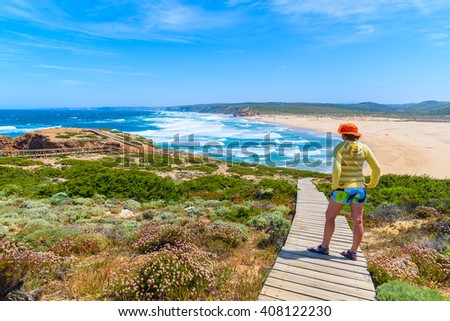 Young woman tourist on walkway to Praia do Bordeira beach and beautiful blue sea view, Algarve region, Portugal