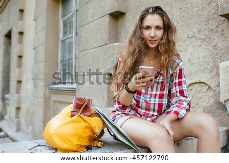 Young woman tourist resting and looking at the phone