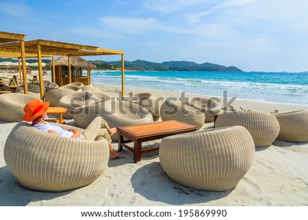 Young woman tourist sits in a beach bar at Porto Giunco bay, Sardinia island, Italy